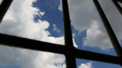 Prison bars and blue sky, pan shot Stock Footage