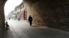 Elderly walking through ancient city gate Stock Footage