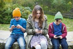 three kids with phones - stock photo