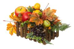Composition from artificial fruits and autumn leaves in wooden box. Stock Photos