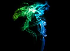 Colored smoke on a dark background Stock Photos