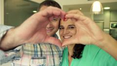 Portrait of happy couple showing heart symbol with hands at home HD Stock Footage