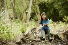 Girl birdwatching. Sitting on a tree stump holding binoculars. Stock Photos