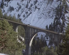 Passenger train towards Davos, crossing the Wiesen Viaduct + pan chalet Stock Footage