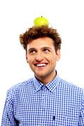 happy young man with green apple on his head - stock photo
