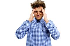 young man having headache over white background - stock photo
