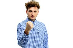 Serious angry man showing fist over white background Stock Photos