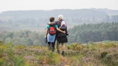 A couple standing on a path looking at the view over wooded hills Stock Photos