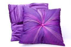 two mauve scatter cushions with intricate patterns - stock photo
