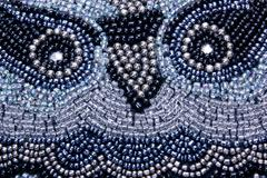 Face of owl embroided in beads on scatter cushion Stock Photos