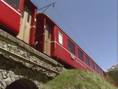 Passenger train direction St.Moritz approaching + crossing viaduct - low angle - stock footage