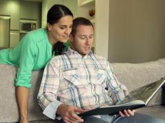 Young couple watching photos in album on sofa at home NTSC - stock footage