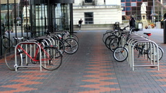 Bicycle parking lot in front of glass building Stock Footage