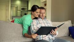 Young couple watching photos in album on sofa at home HD Stock Footage