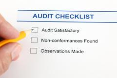 Audit checklist and human hand with pencil. Stock Photos