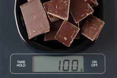 Broken dark chocolate on kitchen scale Stock Photos