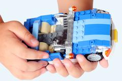 lego blue roadster in child's hands - stock photo