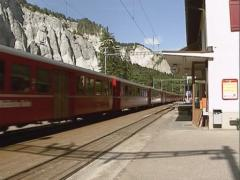 Glacier Express train passing Versam station in the  Ruinaulta or Rhine Canyon Stock Footage