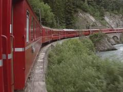 Vehicle shot Glacier Express - red carriages riding in a curve along river Rhine - stock footage