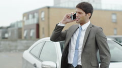 Portrait of successful businessman stood next to a car using mobile  Stock Footage