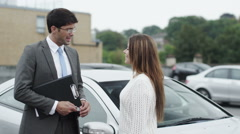Happy woman takes keys to her new car from the dealer Stock Footage