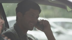 Happy couple sat in car phoning home to share good news  Stock Footage