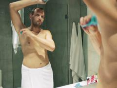 Man in towel applying antiperspirant on his armpit in the bathroom NTSC Stock Footage