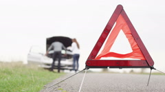 Couple trying to fix broken down car with hazard triangle in the foreground - stock footage