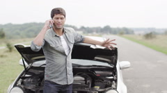 Stranded man with broken down car calls for help  Stock Footage