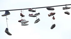 Pairs of shoes hang tossed telephone wire, sneakers power lines, click for HD - stock footage