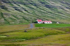 icelandic nature landscape with mountains and dwellings - stock photo