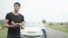 Attractive man lost with a broken down car at the roadside Stock Footage