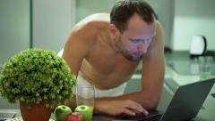 Man in towel using laptop and drinking juice after shower in kitchen HD Stock Footage