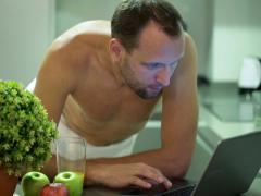 Man in towel using laptop and drinking juice after shower in kitchen NTSC Stock Footage
