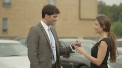 attractive young woman receives keys for her new car with a handshake - stock footage