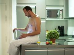 Man in towel finish working on laptop walking away from kitchen NTSC Stock Footage