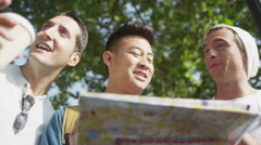 Casual male friends looking at map and trying to find their way around the city - stock footage