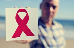 young man with a picture of a red ribbon for the fight against aids - stock photo