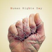 Man hand tied with wire and the text human rights day Stock Photos