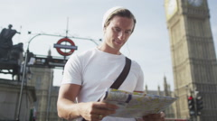Casual young man looking at London map & trying to find his way around the city Stock Footage