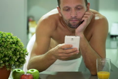 Man in towel sending, texting sms on smartphone after shower in kitchen NTSC Stock Footage