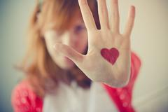Girl showing a drawn heart on her palm, close up Stock Photos