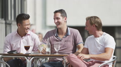 Happy casual male friends relaxing with drinks at street cafe in the city - stock footage
