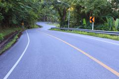 curve of asphalt road in mountain high ways and jungle beside use for land tr - stock photo