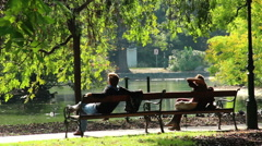 Romantic dating man and woman separately in park benches meeting, click for HD - stock footage