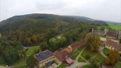 Medieval European castle red rooftops, aerial shot, brown trees, click for HD Stock Footage