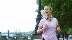 Female runner in the city with headphones stops to get her breath back Stock Footage