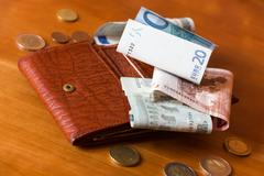 Wallet and some money on a wooden table Stock Photos