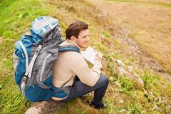 smiling man with backpack hiking - stock photo