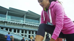 Sporty woman in urban environment ties her shoelaces  in preparation for workout - stock footage
